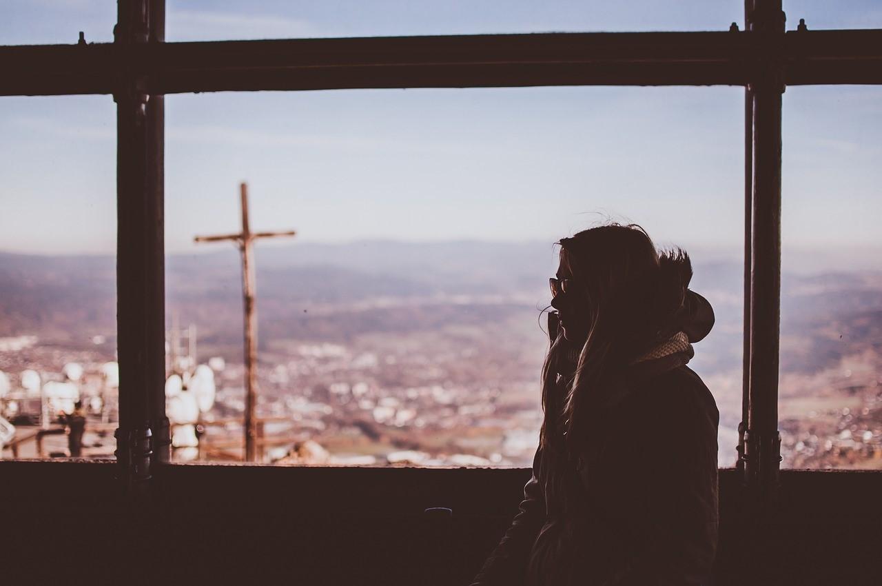 Imagen que contiene ventana, mujer, sentada, abrigo, azul, paisaje